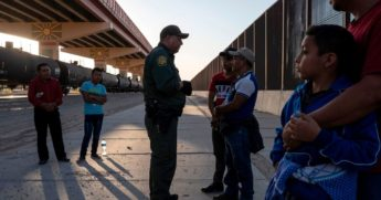 U.S. Customs and Border Protection agent questions a migrant about a boy he is traveling with, May 16, 2019, in El Paso, Texas.