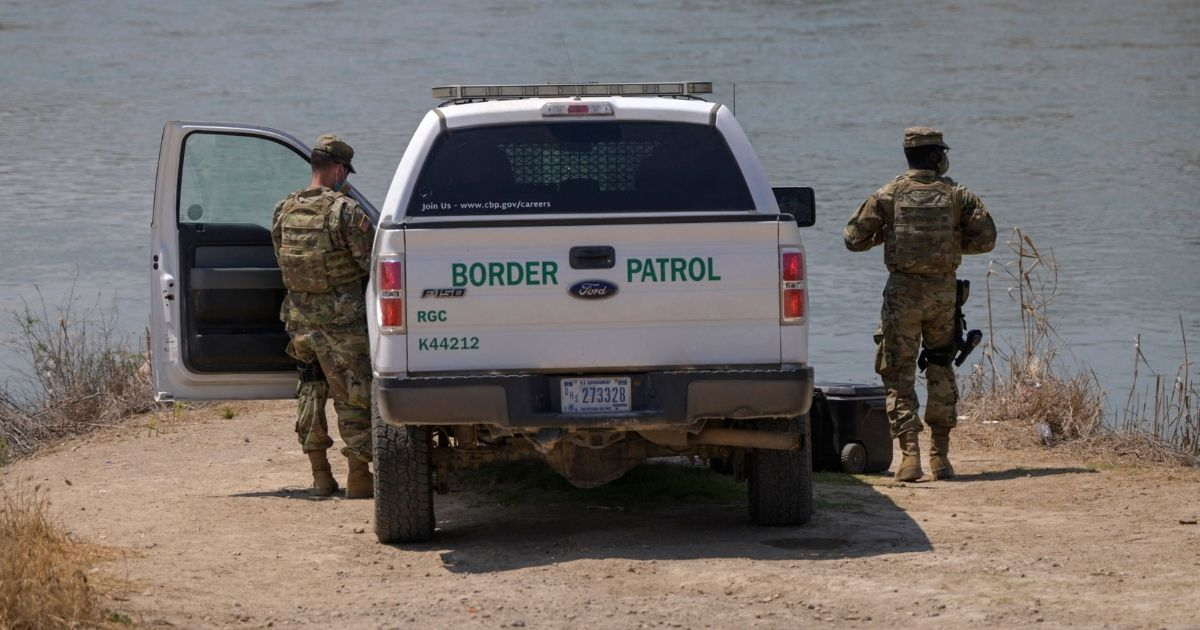 Border Patrol agents stand before the Rio Grande river and a suburb of the Mexican city of Ciudad Miguel Aleman, in the southern Texas border city of Roma, on March 27, 2021.