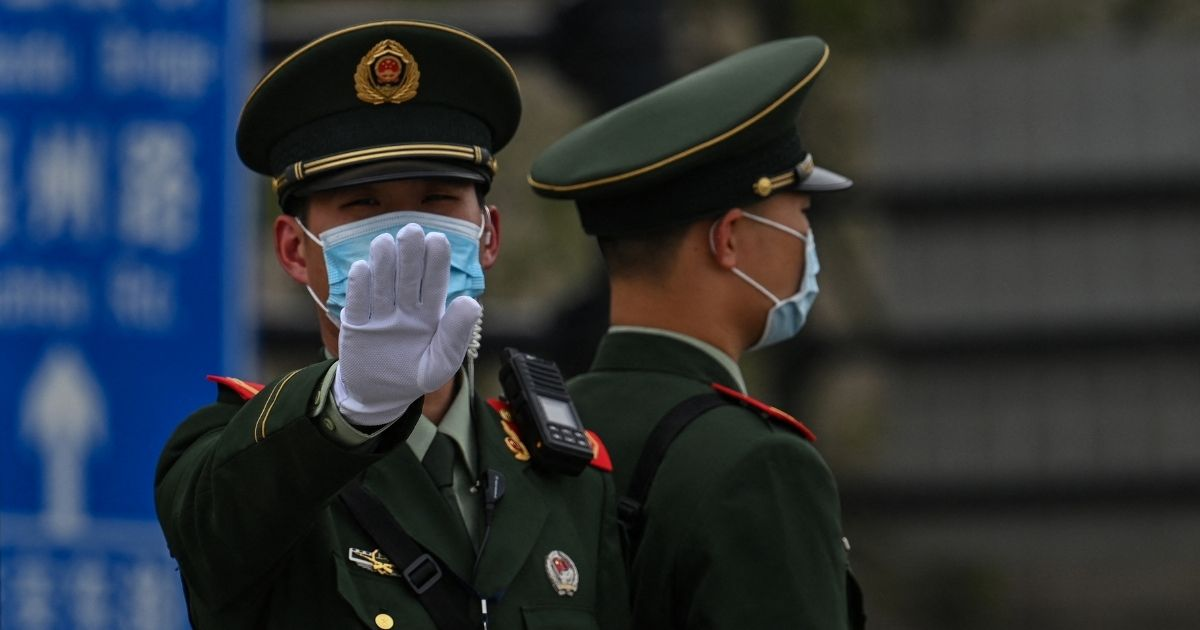 A Chinese paramilitary police officer gestures on the promenade of the Bund along the Huangpu River in Shanghai on April 16.
