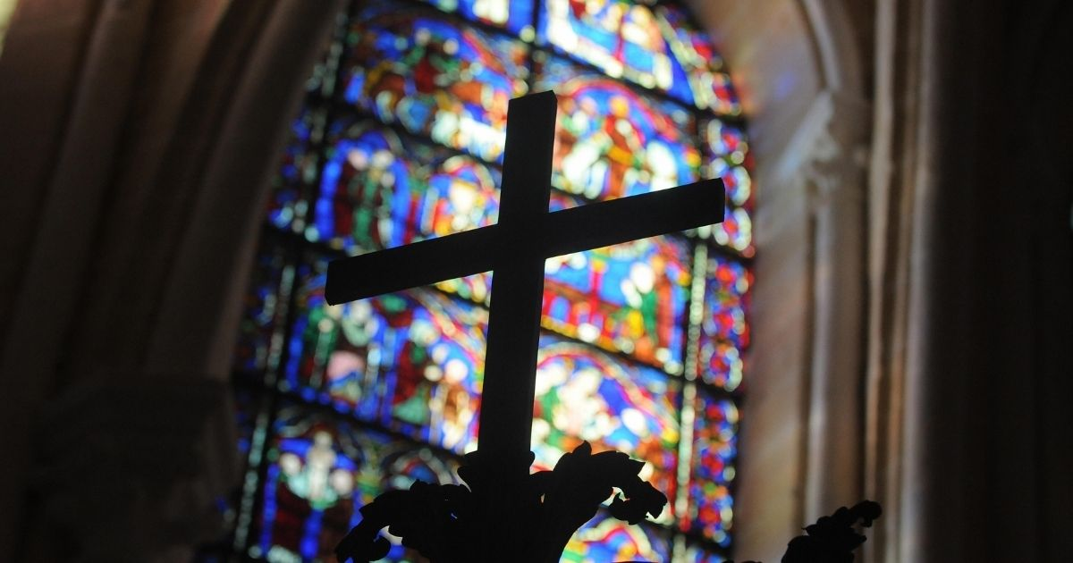 This photo taken on Aug. 26, 2009, shows a cross and a stained glass window in one of the restored chapels of the Cathedral of Chartres, 90 kilometers (55 miles) southwest of Paris.