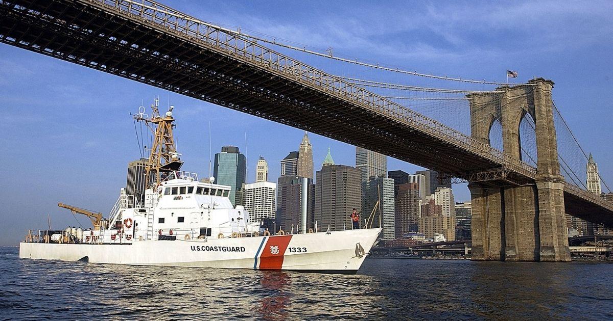 The Coast Guard Cutter Adak patrols past the Brooklyn Bridge along the East River in New York City on Aug. 22, 2002.