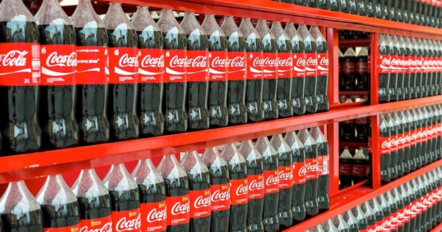 Bottles of Coca-Cola are pictured on shelves in the stock image above.