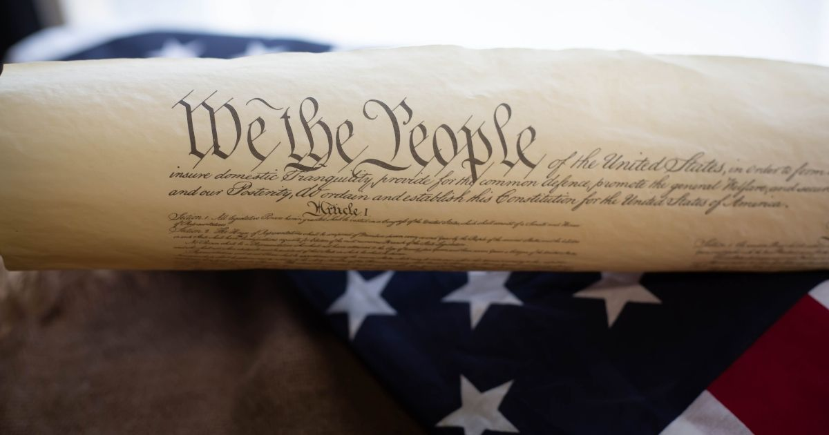 The Constitution is pictured on an American flag in the stock image above.