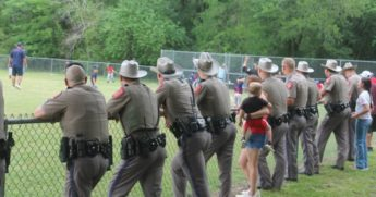Troopers from the Texas Department of Public Safety attend their wounded colleague's son's baseball game on Tuesday.