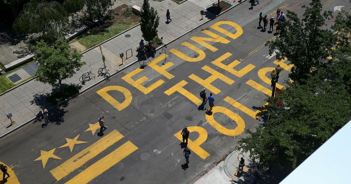 People walk down 16th street after 'Defund The Police' was painted on the street near the White House on June 8, 2020, in Washington, D.C.