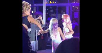 A man in drag directs two young children at Palace South Beach, an LGBT nightclub in Miami Beach, Florida.