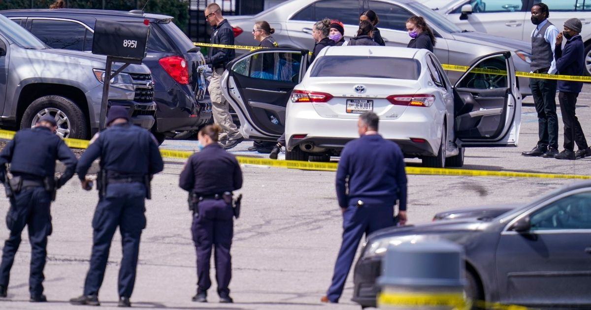 Law enforcement officers confer at the scene on Friday in Indianapolis, where multiple people were shot at a FedEx Ground facility near the Indianapolis airport.