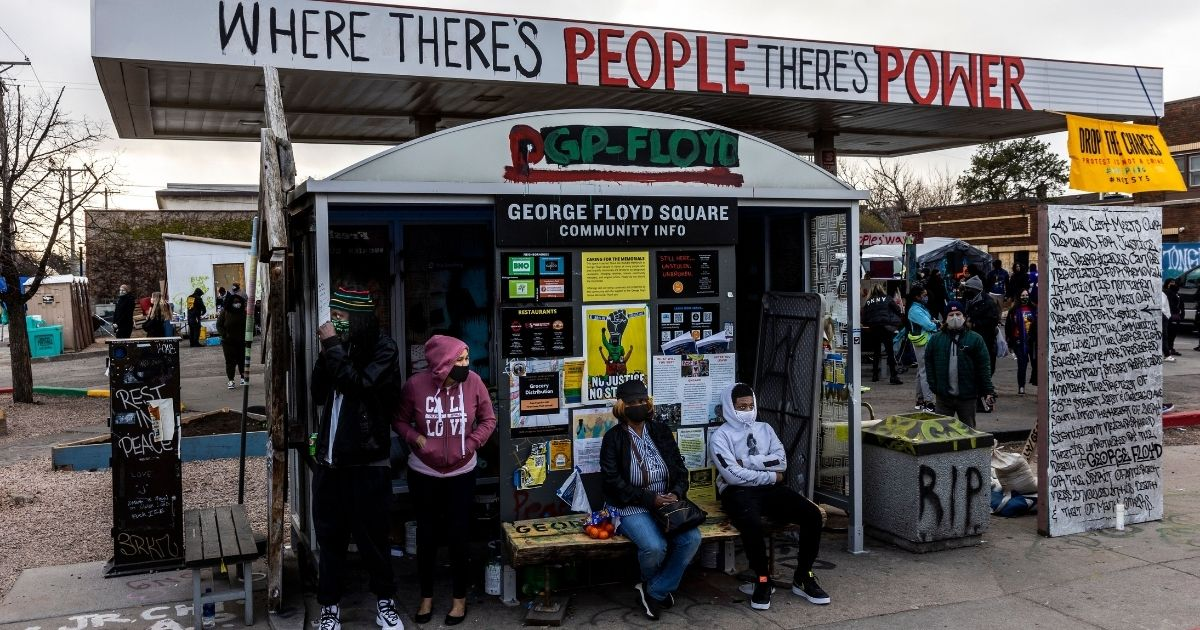 People sit at a bus stop at George Floyd Square in Minneapolis on Wednesday.