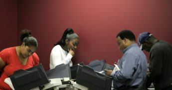 People cast their absentee ballots using electronic voting machines during early voting on Oct. 1, 2008, in Toledo, Ohio.