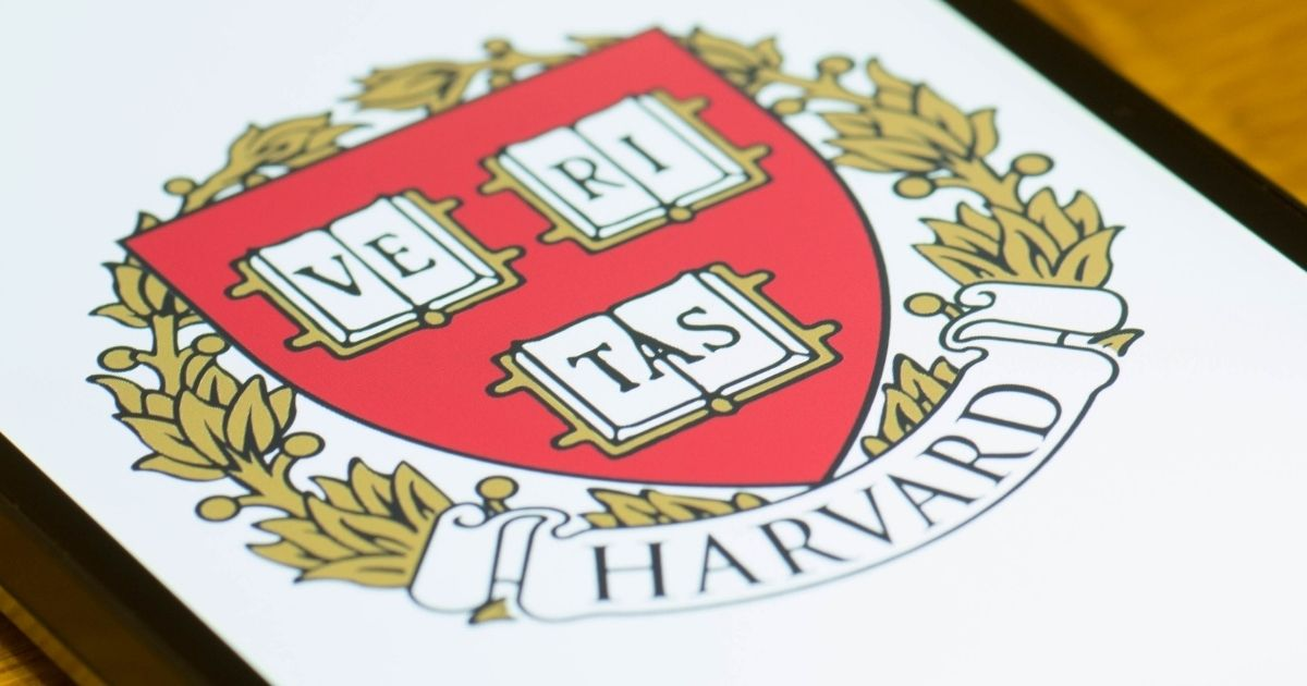 The Harvard University coat of arms is pictured on a smartphone in the stock image above.