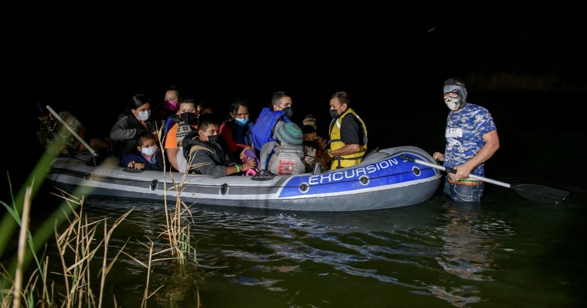 "A ""coyote"" people smuggler, right, guides an inflatable boat carrying migrants from Central America arriving illegally from Mexico to the U.S. on the Rio Grande river at the border city of Roma on March 29, 2021."