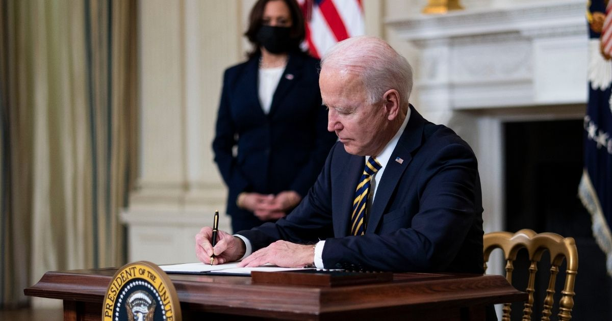 President Joe Biden signs an executive order on the economy with Vice President Kamala Harris on Feb. 24, 2021, in the State Dining Room of the White House in Washington, D.C.