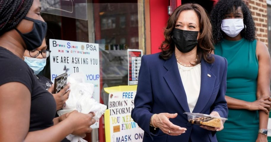 Kamala Harris holds a slice of cake outside Brown Sugar Bakery