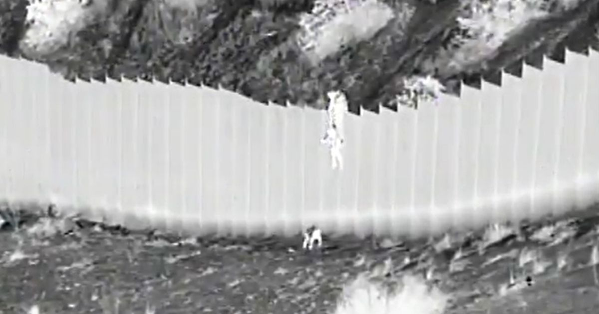Two young children are dropped from the border wall into the U.S.