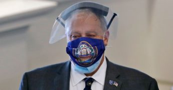 Terry Pfaff, chief operating officer of the New Hampshire General Court, wears a face shield and a protective mask adorned with a design of the state seal prior to a session at the State House in Concord on June 16.