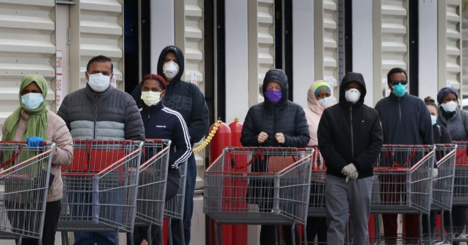 Customers wear face masks as they line up to enter a Costco Wholesale store on April 16, 2020, in Wheaton, Maryland.