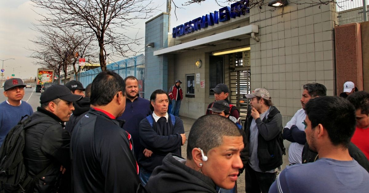 Mexican workers stand outside the Hunts Point Food Distribution Center at the end of their overnight shift in the Bronx, New York, on March 13, 2012.