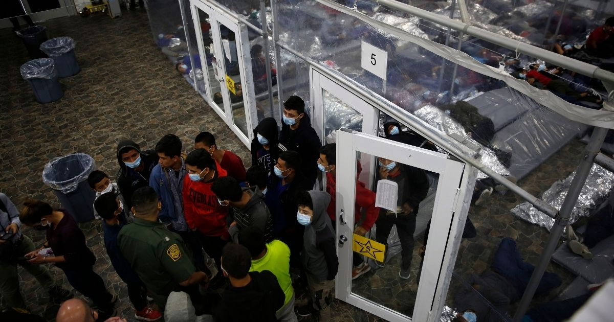 Minors talk to an agent outside a pod at the Department of Homeland Security holding facility run by the Customs and Border Patrol (CBP) on March 30, 2021, in Donna, Texas.