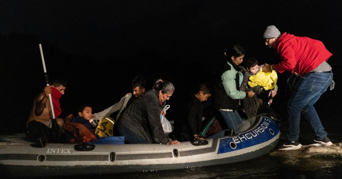 Asylum-seeking migrants' families disembark from an inflatable raft after crossing the Rio Grande river into the United States from Mexico on Friday in Roma, Texas.