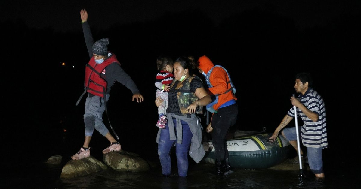 A group of migrants arrives in the U.S. after crossing the Rio Grande in a raft piloted by smugglers on March 30 in Roma, Texas.