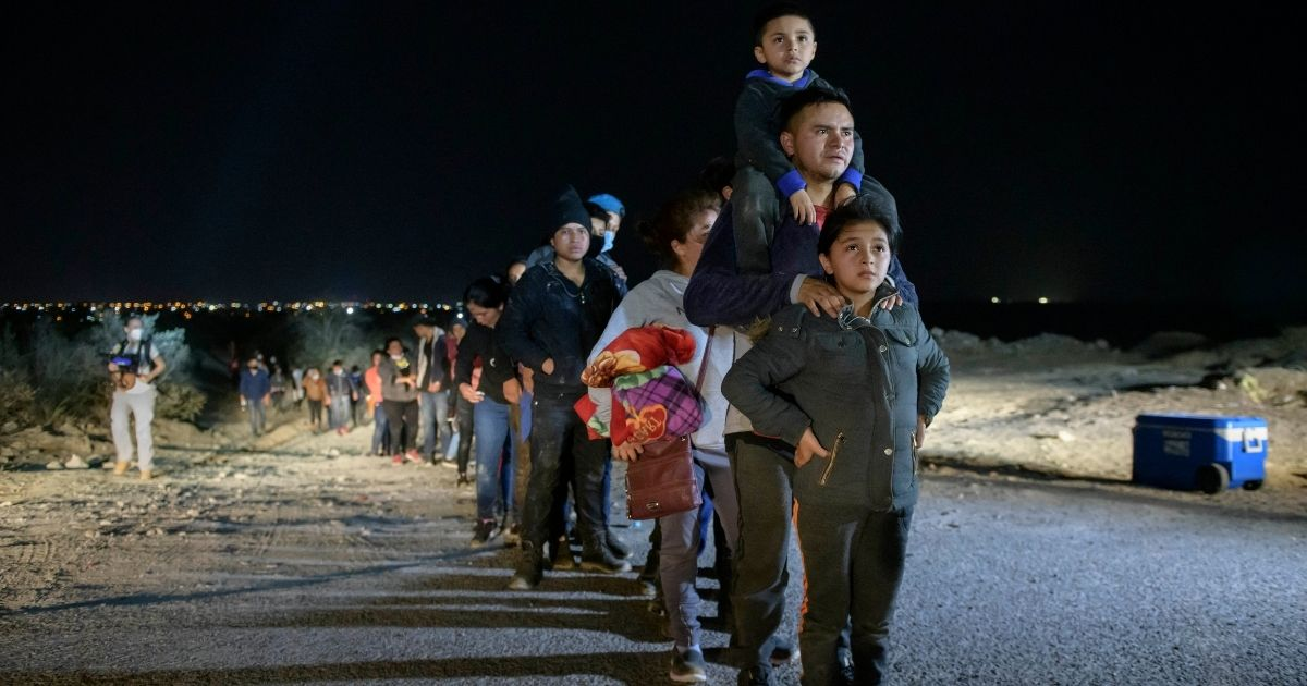 A family of immigrants who arrived illegally across the Rio Grande river from Mexico stand in line at a processing checkpoint on March 27, 2021, before being detained at a holding facility by border patrol agents in the border city of Roma.