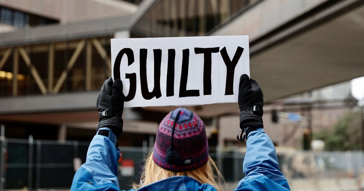 """A protester holds a """"guilty"""" sign outside a courthouse in Minneapolis on April 19, 2021."""