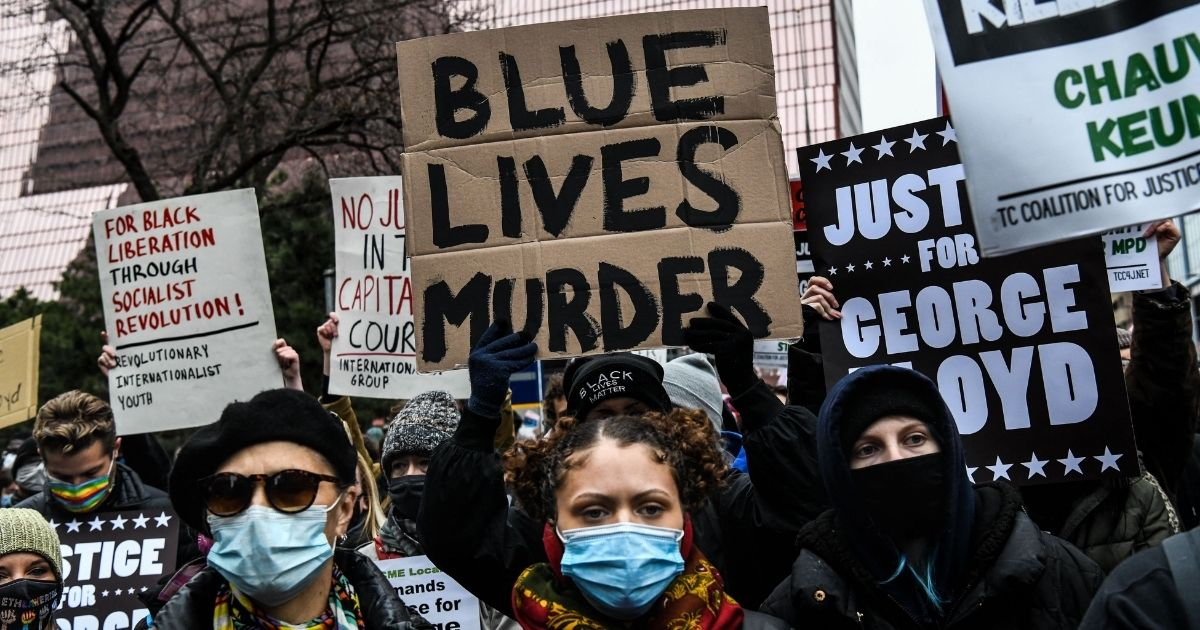 People hold placards as they protest during the trial of Derek Chauvin in Minneapolis on Monday.