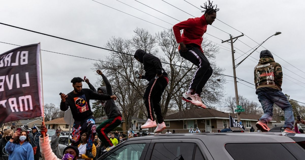 Rioters jump on top of a police car Sunday during demonstrations that broke out after an officer shot and killed Daunte Wright in Brooklyn Center, Minnesota.