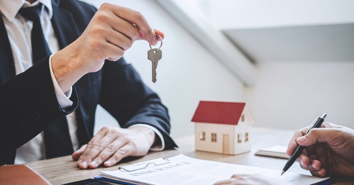 In the stock image above, a real estate agent is seen giving house keys to a client.