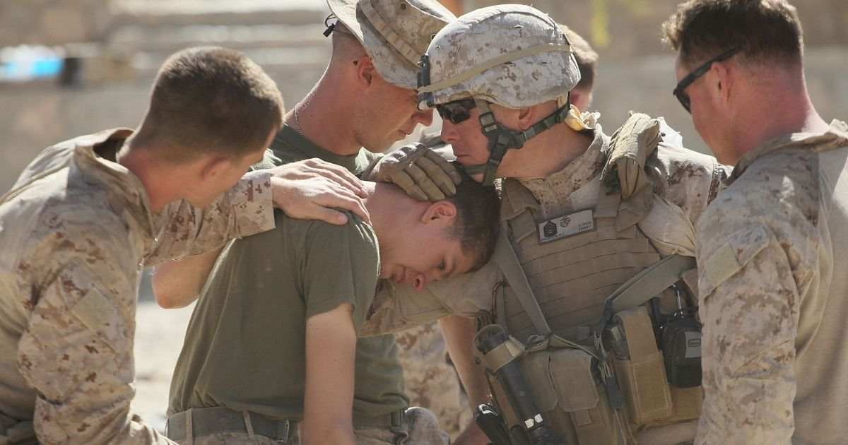 Marine GySgt. David Pruden of Fairfield, California, comforts LCpl. Nick Reoyo of Kimberly, Wisconsin, with India Battery, 3rd Battalion, 12th Marine Regiment after Reoyo learned that his friend and roommate LCpl. Francisco Jackson of Elizabeth, New Jersey, was killed while on patrol near Forward Operating Base (FOB) Zeebrugge on Oct. 19, 2010, in Kajaki, Afghanistan.