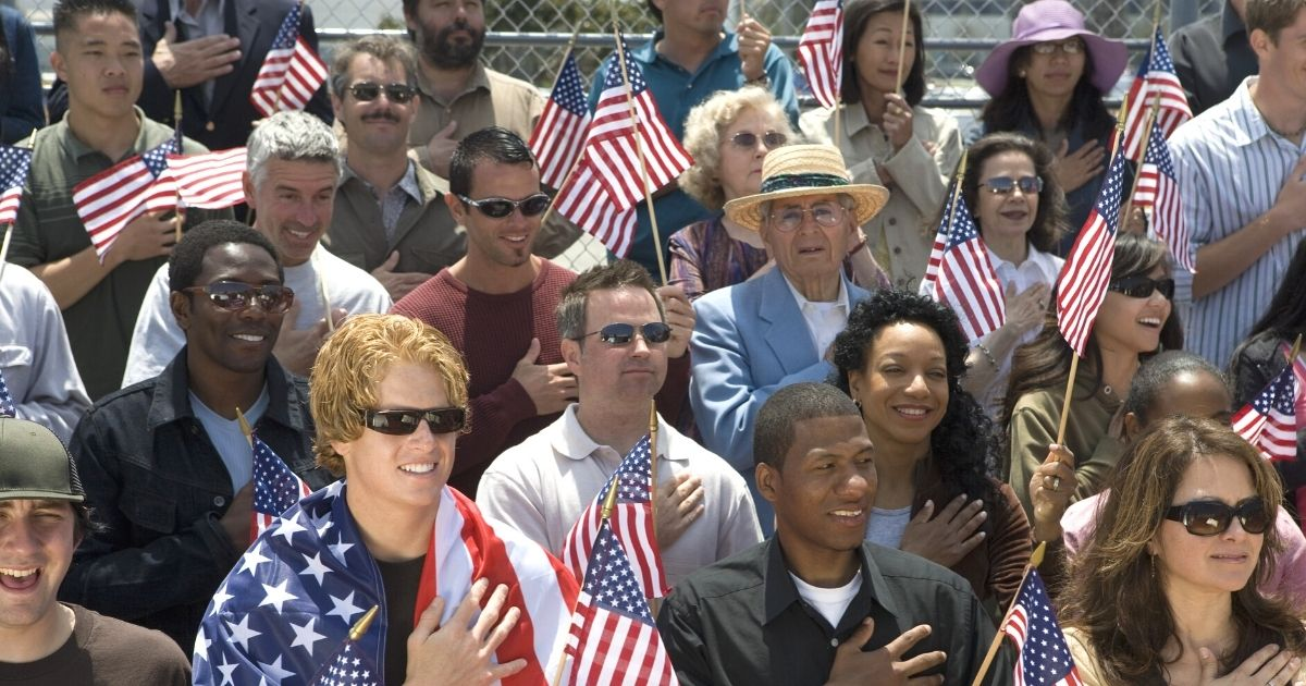 A diverse group of people singing the national anthem and holding American flags.