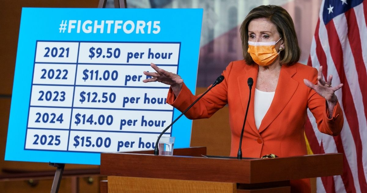 House Speaker Nancy Pelosi stands beside a chart outlining a path to a $15-per-hour minimum wage during her weekly news conference at the Capitol in Washington on March 11.