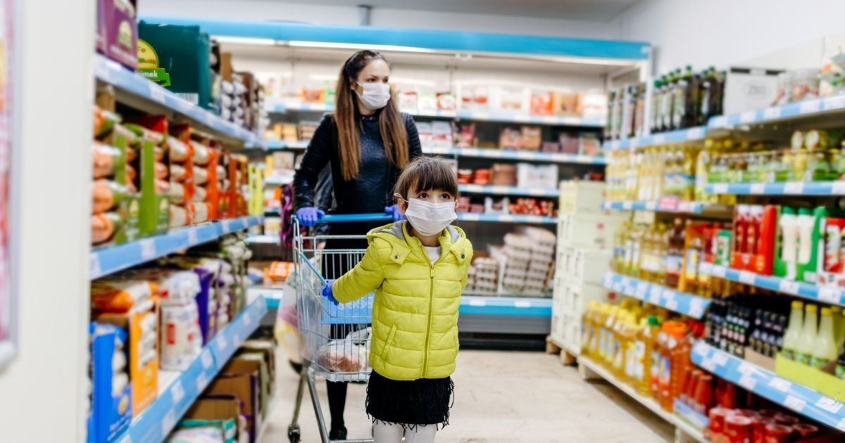 A mother and her daughter wear masks in the stock image above.