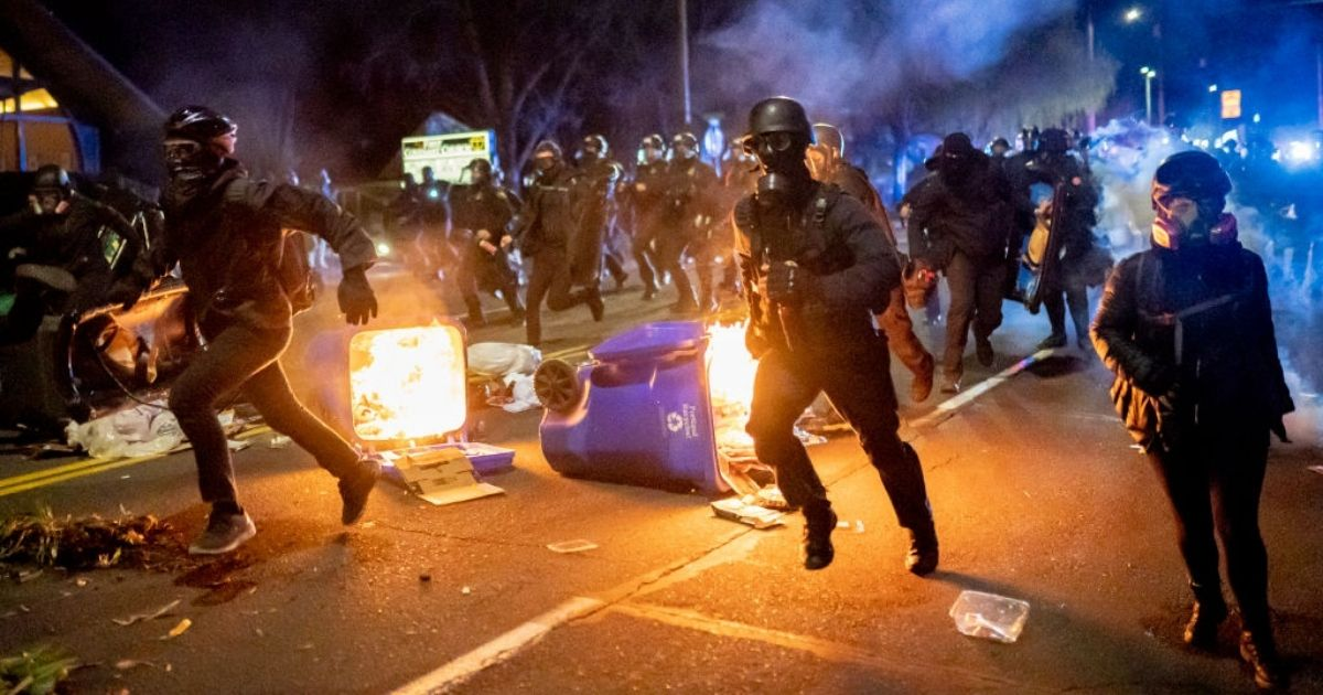 Portland police officers chase rioters on April 12, 2021, in Portland, Oregon.