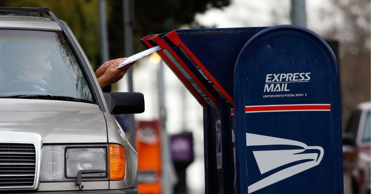 A postal customer drops letters into a mailbox in San Francisco.