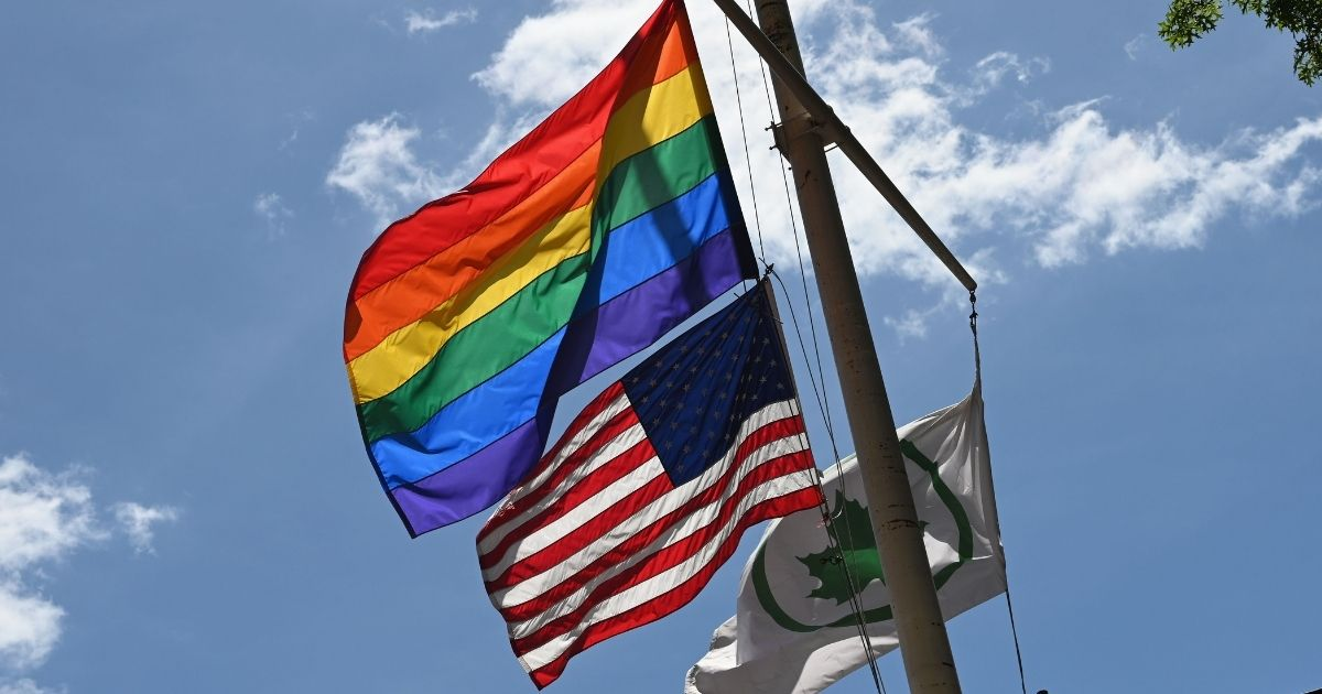 Pride flag above an American flag