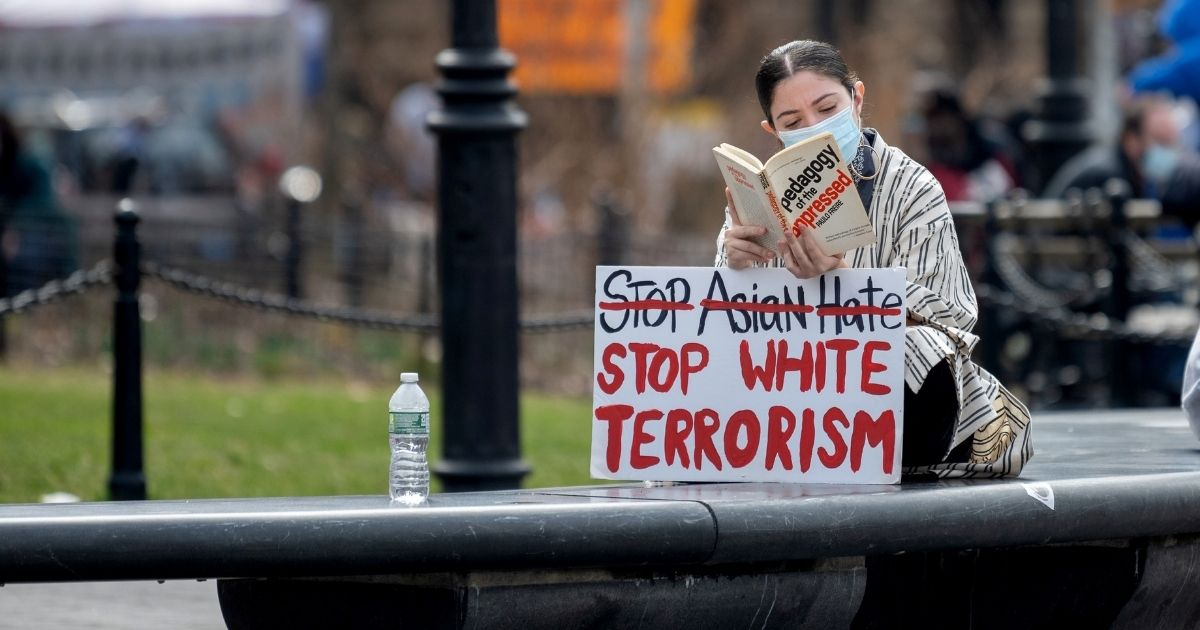 """A woman reading a book sits with a a """"stop Asian Hate, stop white terrorism"""" sign in Washington Square Park on March 25, 2021, in New York City."""