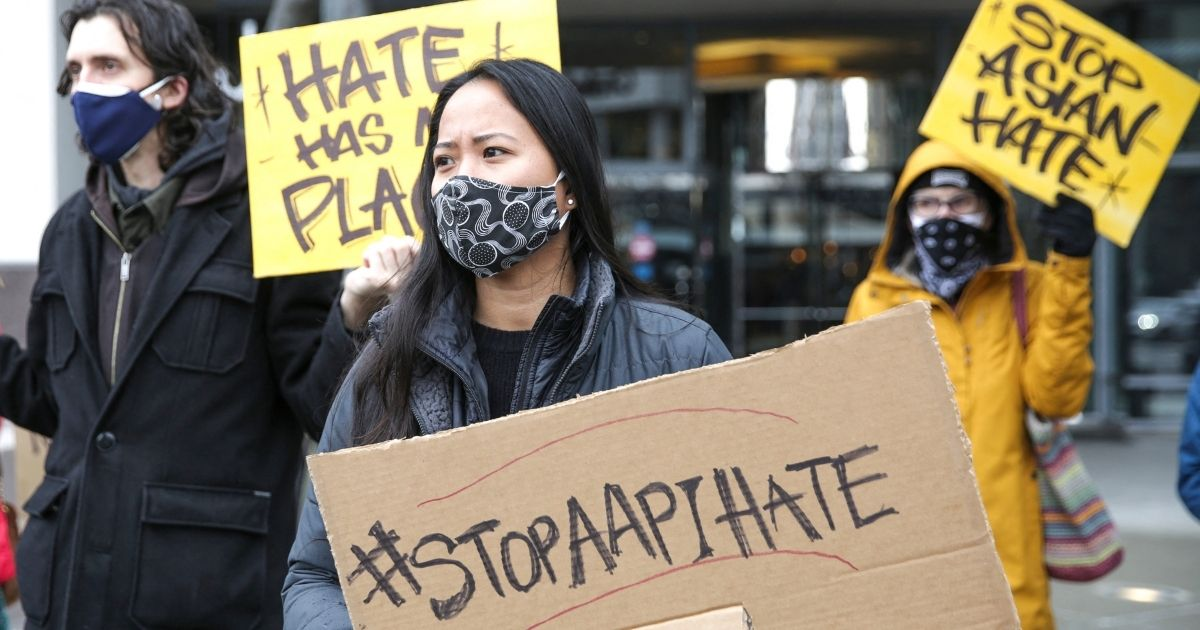 """Trish Villanueva (center) of Seattle holds a sign with the hashtag """"stop AAPI hate"""" during the We Are Not Silent rally organized by the Asian American Pacific Islander (AAPI) Coalition Against Hate and Bias in Bellevue, Washington, on March 18, 2021."""