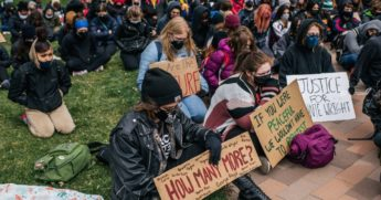 High school students from across Minneapolis sit in silence during a statewide walkout demonstration on Monday.