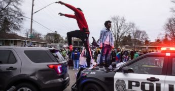 On man stands on the hood of a police car while another jumps to a nearby police vehicle.
