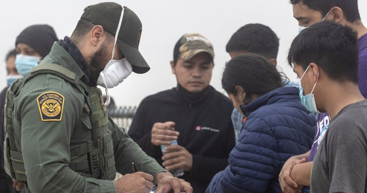 A Border Patrol agent takes te names of illegal immigrants from Central America arrested Saturday in La Joya, Texas.
