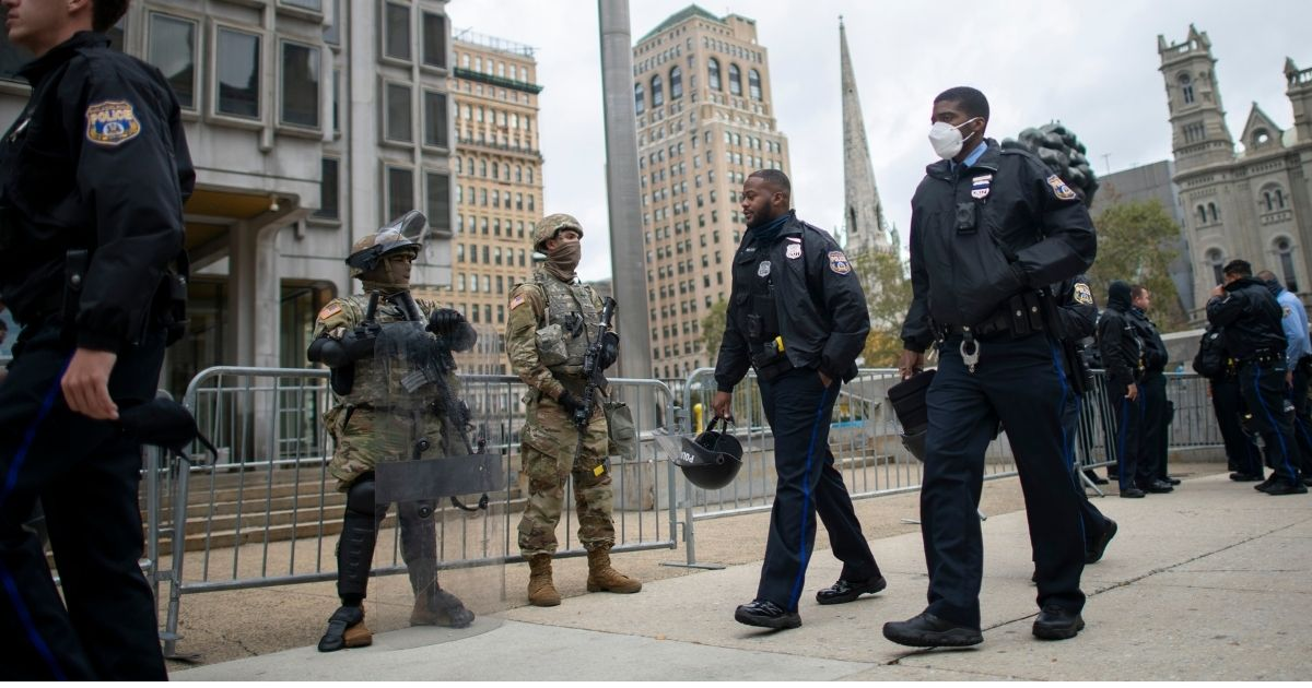 Police officers walk past as members of the National Guard patrolling the city in an October file photo,