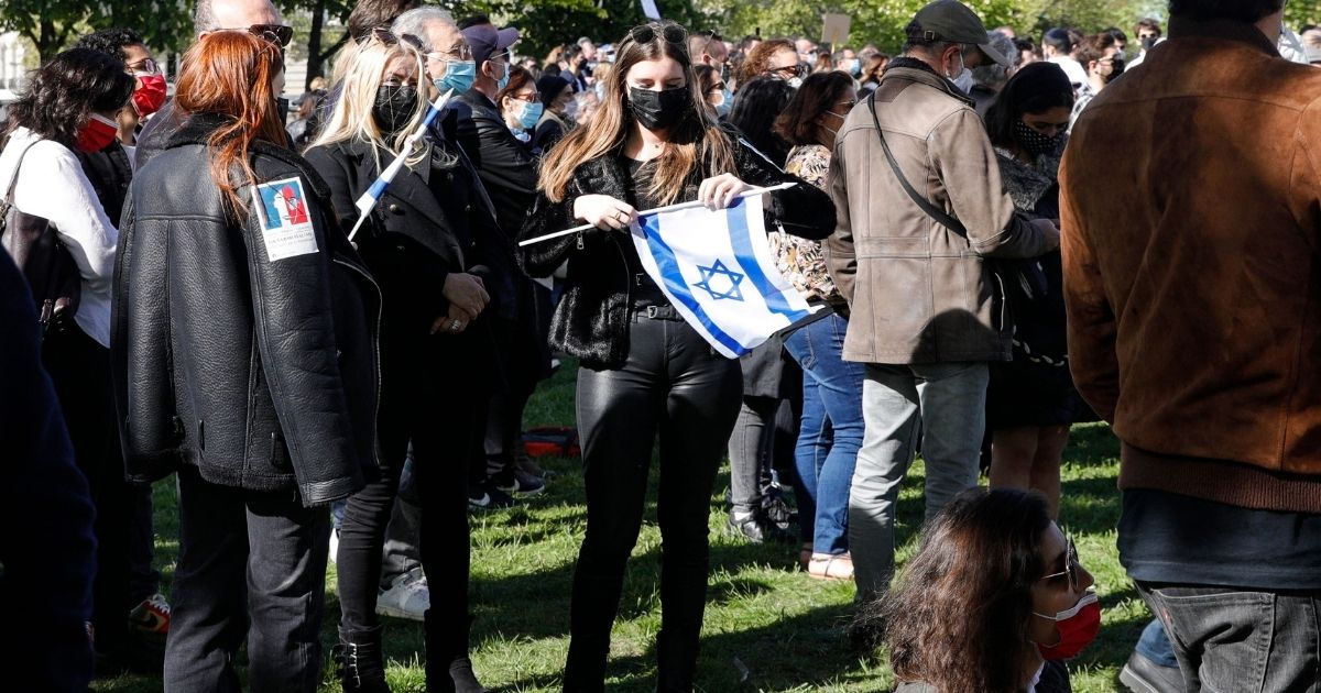A woman holds a flag of Israel as people gather in Paris on April 25, 2021, to ask for justice for the late Sarah Halimi, a 65-year-old Orthodox Jewish woman who was killed in 2017 by her neighbor, Kobili Traoré.