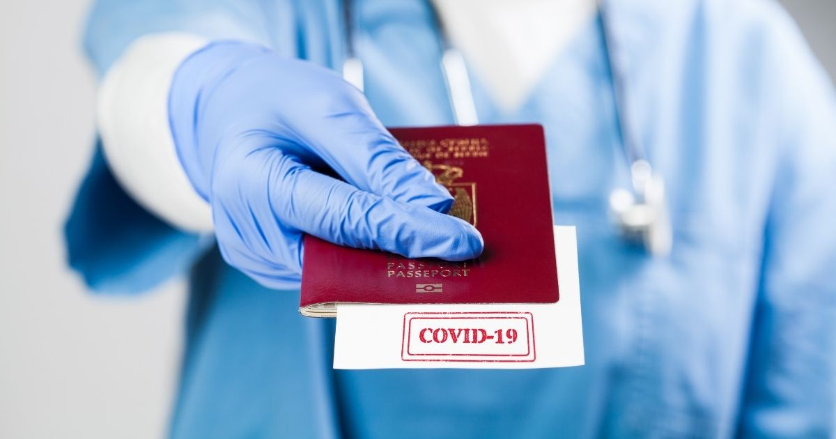 """A health professional is seen holding a COVID vaccine """"passport"""" in the stock image above."""