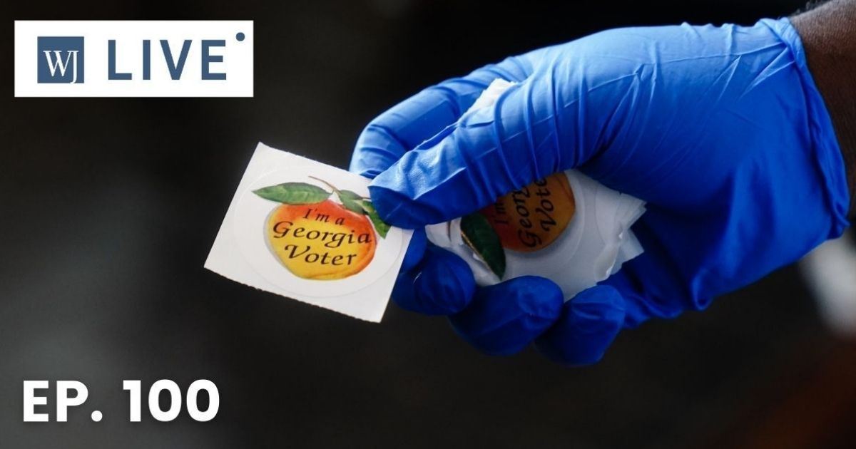 """A polling place worker holds an """"I'm a Georgia Voter"""" sticker to hand to a voter on June 9, 2020, in Atlanta."""