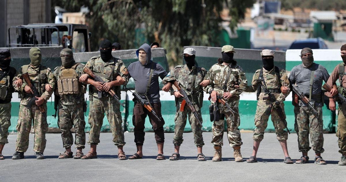Jihadists of former al-Qaida affiliate Hayat Tahrir al-Sham block demonstrators from approaching the Bab al-Hawa crossing between Turkey and Syria's northwestern Idlib province during a protest on Sept. 20, 2019.