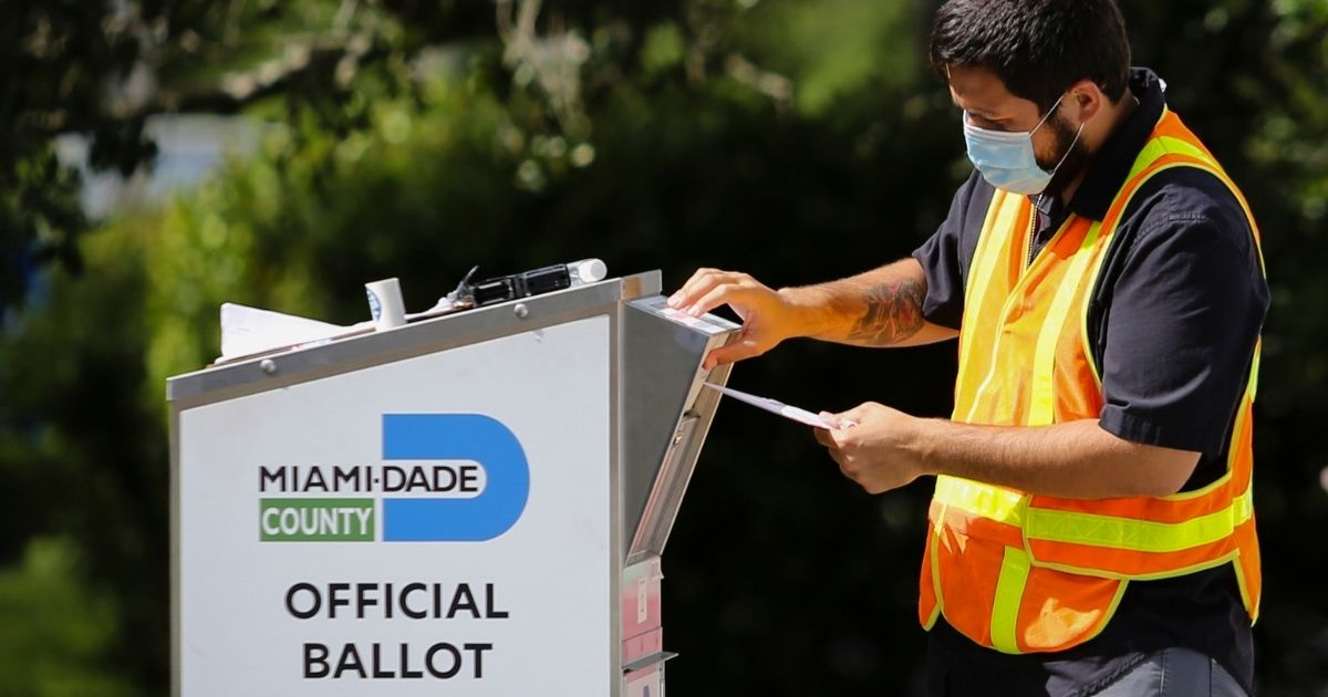 A poll worker drops off a mail-in ballot at the Miami-Dade County Election Department in Miami on Nov. 3, 2020.