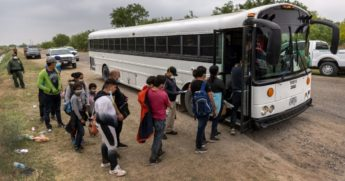 Central American migrants board a US Customs and Border Protection bus after crossing the border from Mexico on April 13, 2021, in La Joya, Texas.