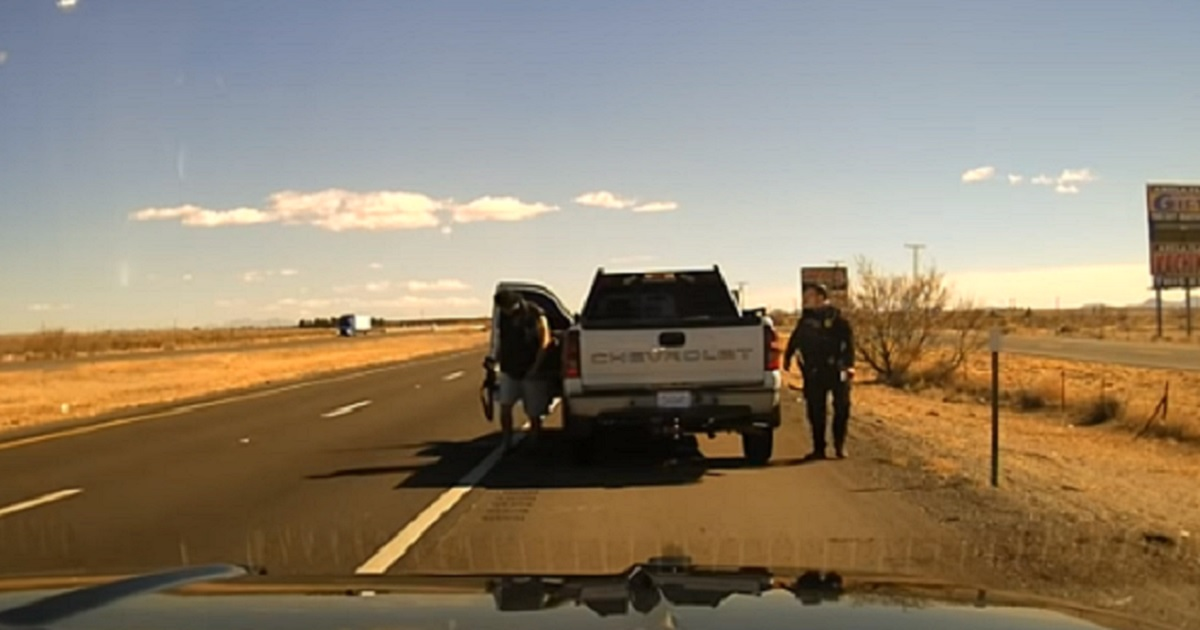 A New Mexico State Police officer stands on the passegenger side of a pickup truck as a man gets out of the vehicle on the driver's side.