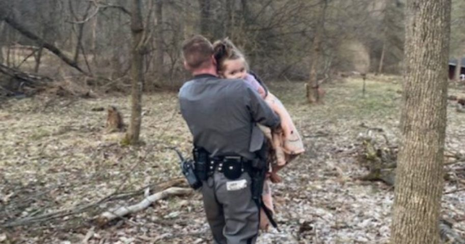 Officer Brian Hotchkiss carries a lost 2-year-old girl to safety.